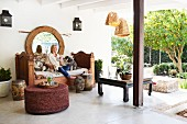 Relaxing on a veranda; woman and dogs on antique bench, rattan pouffe and view into garden to one side