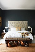 Double bed with tall, upholstered headboard against black-painted wall, row of handbags under cord-seat bench at foot of bed