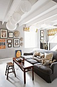 Antique bench in front of dogs on grey sofa in rustic living room with several spherical paper lampshades hanging from white wood-beamed ceiling