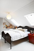 Twin beds with black wooden frames under sloping ceiling with white wood panelling