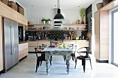Metal, retro-style chairs around shabby dining chic table in designer kitchen