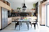 Metallstühle im Retrostil um Esstisch im Shabby Look in Designerküche