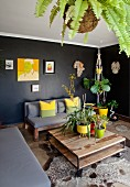 Planters on rustic coffee table, animal-skin rug on floor and couch against black wall
