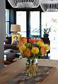 Tropical bouquet of pincushion proteas in glass vase on table; lounge area in background