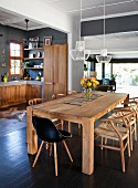 Black shell chair and classic, solid wood chairs around solid wood table in interior with open-plan kitchen