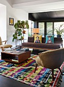 Fifties-style armchair and coffee table on brightly patterned rug and couch with brown cushions in open-plan interior