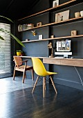 Classic yellow shell chair at minimalist desk below wooden shelves on black-painted wall