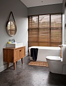 Modernes Bad mit freistehender Badewanne vor Fenster und geschlossenr Jalousie, seitlich Waschtischmöbel aus Massivholz