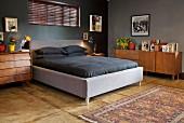 Elternschlafzimmer mit Doppelbett und schwarzer Bettwäsche in dunkel getöntem Raum, Sideboard aus Massivholz