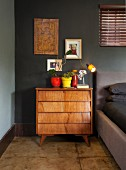 Colourful plant pots and retro table lamp on fifties-style, solid wood chest of drawers in bedroom with black-painted wall