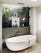 Free-standing designer bathtub against grey facing formwork with wall-mounted taps in contemporary bathroom with pattern of light and shadow on wall