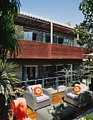 Pale wicker outdoor furniture on sunny wooden terrace opposite modern house with encircling balcony and wooden balustrade on upper storey