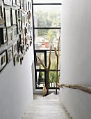 Narrow stairwell with framed pictures on wall, floor-to-ceiling glass facade at foot of staircase with view of terrace