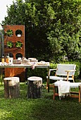 Set table, tree stump stools and armchair in garden; wooden panel with potted plants in circular apertures in background