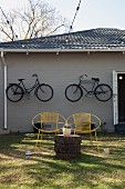 Yellow, vintage wire chairs and tree stump table in front of grey wooden house with bicycles hung on facade