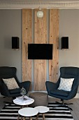 Side tables and swivel armchairs in front of flatscreen TV on wooden panels on wall flanked by loudspeakers