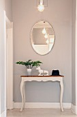Oval mirror above dachshund bookends on vintage console table at end of hallway