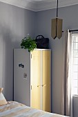 White locker with pastel yellow doors used as vintage cupboard in bedroom