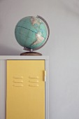 Old globe on white vintage locker with door painted pastel yellow