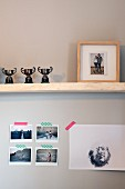 Three trophies and framed photo of couple on wooden shelf above photos attached to wall with washi tape