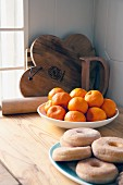 Tangerines and ring doughnuts on kitchen worksurface; wooden boards and rolling pin in background