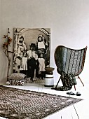 Textiles with graphic patterns, mesh easy chair, painted wooden stool in front of life-sized black and white photo of African family