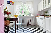 White country-house kitchen with black and white chequered floor, old wooden table in dining area and retro chairs