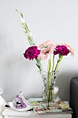 Venetian mask and glass vase of purple carnations and delicate pink gerbera daisies on white side table
