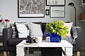 White and grey seating area with sofa, DIY coffee table, bright blue glass vase as focal point and gallery of pictures in background
