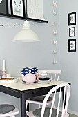 Small, black and white dining area in front of grey-painted wall with origami garland and gallery of black-framed pictures