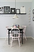 Black and white dining area with vintage chairs and colour-coordinated gallery of pictures on grey-painted wall
