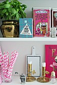 Feminine arrangement of kitchen shelves with pink accents and brass ornaments