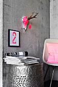 Mit Neon-Pink bemalter Geweihschädel und Typo-Bild an Betonwand über Tonnenmöbel aus gehämmertem Metall