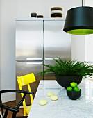 Marmortisch mit gelbem und schwarzen Stühlen, im Hintergrund Edelstahl-Kühlschrankkombi