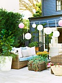 Garland of lanterns and rattan sofa set with flower arrangement on terrace of contemporary house with dark grey weatherboard facade