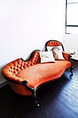 Antique sofa with orange velvet upholstery and scatter cushion with bird motifs on dark wooden floor