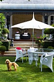 White wicker chairs and glass table below parasol in front of veranda steps with dog on lawn in foreground
