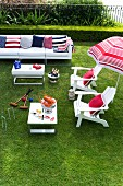 White outdoor furniture and accessories in red, white and blue on lawn
