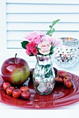 Rose in mercury glass vase and apple ornaments on red plate