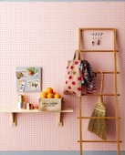 Cloth shopping bag and hand brush hung on wooden ladder next to box of oranges on bracket shelf on pink perforated wall