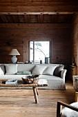 Helles Hussen-Sofa mit Kissen, davor rustikaler Holz Couchtisch im Wohnzimmer einer Hütte