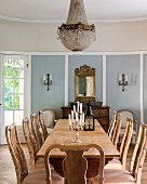 Long rustic wooden table and chairs with carved backrests in dining room of elegant country house with candlesticks on table and candle sconces