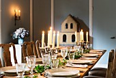 Festively set, candlelit table with model of house in background