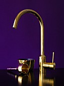 Brass, designer tap fitting and brass-coloured utensils (bell and bowl) against violet background