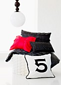 Inspired by Chanel; black and red cushions on white pouffe below spherical pendant lamp