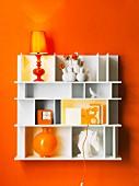 Weisses Regal mit Tischleuchten und Deko-Objekten an orangefarbener Wand