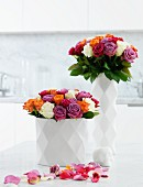 Multicoloured roses in white china vases with diamond-patterned structure surface and petals strewn on white surface