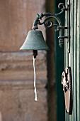 Metallglocke mit verzierter Wandhalterung im Antikstil und runde Schmucktafel an Holzfassade