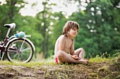 A young girl resting on the floor next to a bicycle