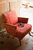 Kopfhörer auf 50er Jahre Sessel mit lachsfarbenem Muster